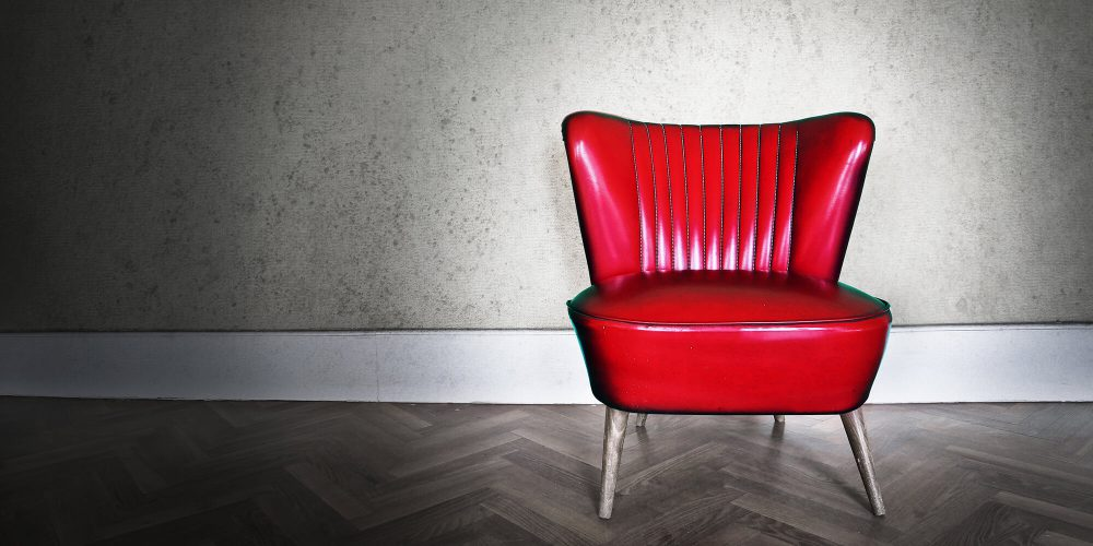 Bright red chair against black and white background